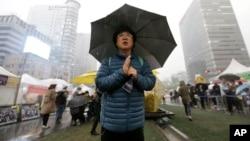 한국 서울에서 세월호 1주년 추모제 행사에서 한 추모객이 희생자들의 명복을 빌고 있다.