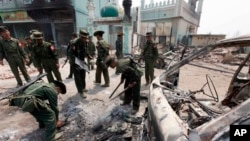Tentara Burma membersihkan rongsokan mobil yang hancur dalam kerusuhan sektarian di Meikhtila, wilayah Mandalay, sekitar 550 kilometer sebelah utara ibukota Burma, Rangoon (23/3). Tentara Burma mengendalikan situasi di wilayah ini setelah beberapa hari rusuh, dengan terus melakukan patroli.