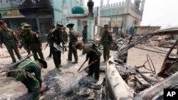 Binh sĩ Miến Điện dọn dẹp mảnh vỡ của xe cộ bị phá hủy sau các vụ bạo động sắc tộc giữa tín đồ Hồi giáo và Phật giáo ở thành phố miền Trung Meikhtila, ngày 23/3/2013.
