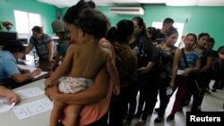 FILE - Women and their children, many who had hoped to reach the U.S., wait in line to register at the Honduran Center for Returned Migrants after being deported from Mexico, in San Pedro Sula, northern Honduras, June 20, 2014.