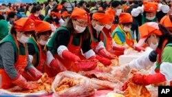 Những người Hàn Quốc và khách du lịch làm kimchi để quyên góp cho các nước láng giềng nghèo trong lễ hội kimchi ở Seoul, Hàn Quốc, thứ Sáu ngày 6/11/2015.