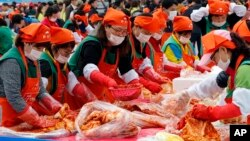 South Koreans and tourists make kimchi to donate to needy neighbors during the Seoul kimchi festival in Seoul, South Korea, Friday, Nov. 6, 2015.