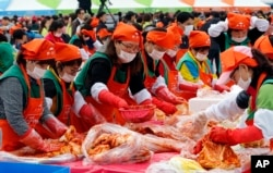 South Koreans and tourists make kimchi to donate to needy neighbors during the Seoul kimchi festival in Seoul, South Korea, Nov. 6, 2015.