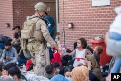 Pasukan Marinir AS memberikan air bersih untuk seorang anak selama evakuasi. (Foto: US Marine Corp via AP)