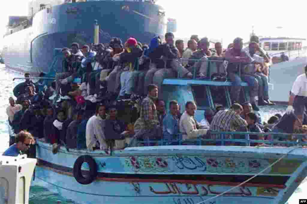 Migrants arrive at the harbor in Ragusa after a boat was intercepted by the Italian coast guard off the city of Ragusa, Italy, Tuesday, Feb. 15, 2011. Overnight, Italian authorities intercepted a boat of 32 people believed to be from Egypt off the coast o