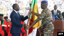 Patrice Talon (L) is handed a national flag during his swearing in as president of Benin at Charles de Gaulle Stadium in the capital Porto-Novo, April 6, 2016.