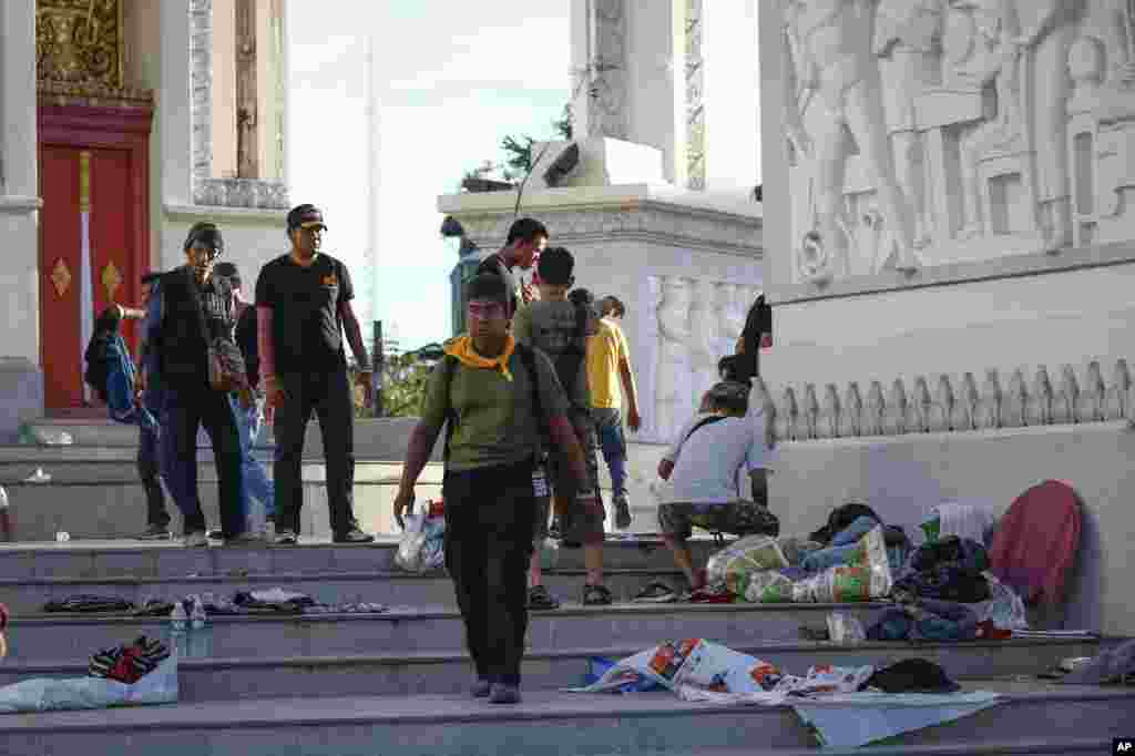 Volunteers from anti-government protesters clean up after an overnight shooting attack at Democracy Monument in Bangkok, Thailand, Thursday, May 15, 2014. Explosions and the overnight shooting attack on opposition demonstrators in Thailand's capital kille