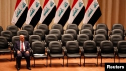 FILE - Iraqi Prime Minister Haider al-Abadi sits during a parliamentary session to vote on Iraq's new government at the parliament headquarters in Baghdad, Sep. 8, 2014.