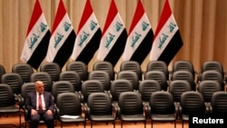 FILE - Iraqi Prime Minister Haider al-Abadi sits during a parliamentary session to vote on Iraq's new government at the parliament headquarters in Baghdad, Sep. 8, 2014. Negotiations between the country's highly polarized political factions have failed to produce a way forward for Iraq.