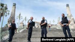 Cuatro policías montan guardia en una gran escalinata de acceso a la estación de tren de Saint-Charles, este domingo 1 de octubre en la ciudad francesa de Marsella.