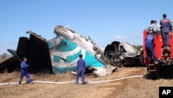 Members of Burma's Fire Brigade team gather near a damaged Air Bagan passenger plane in Heho, Shan State, Dec. 25, 2012.