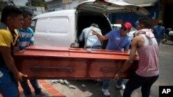 Familiares trasladan el ataúd de Daniel Márquez, víctima de un catastrófico incendio en una cárcel en una estación policial en Valencia, Venezuela, el jueves, 29 de marzo, de 2018.