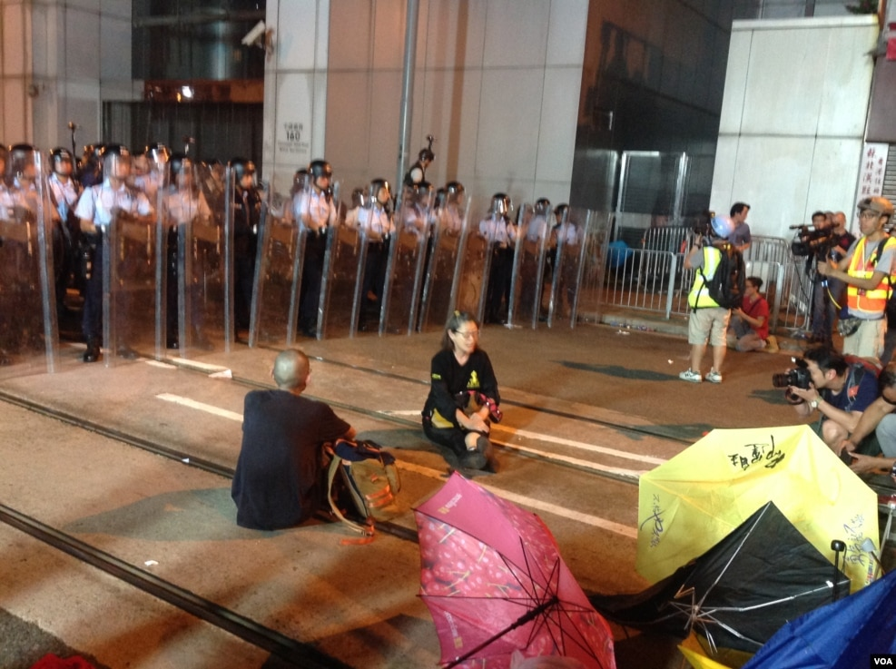 从10点前,在中联办外德辅道西上的警察由手持约一米七高的长盾牌的防暴警察替换到最前排,做好准备清场的准备。示威者则用铁马和雨伞筑成防线,应对警方的清场。另外,在西边街,也有一些示威者与警方对峙,但场面没有在德辅道上紧张。目前,现场仍有近千人。