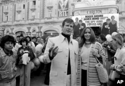 "FILE - In this May 20, 1977 file photo, actor Roger Moore, alias British secret agent James Bond, is accompanied by co-star Barbara Bach as they arrive for the screening of ""The Spy Who Loved Me,"" during the Cannes Film Festival (AP Photo)."