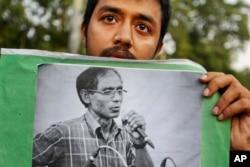 Một sinh viên cầm bức hình chân dung Giáo sư Đại học A.F.M. Rezaul Karim Siddique trong một cuộc biểu tình chống lại việc giết hại ở Dhaka, Bangladesh, ngày 29 tháng 4 năm 2016.