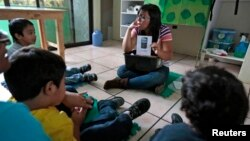 FILE - A teacher talks to children during class at a therapy and development center for autistic kids in Guatemala City.