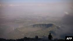 Des volcanologues et des gardes forestiers congolais du parc national des Virunga regardent la vallée du haut du volcan Nyiragongo, au nord de Goma, la capitale provinciale du Nord-Kivu, le 11 juin 2021.