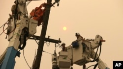 FILE - Pacific Gas & Electric crews work to restore power lines in Paradise, Calif., Nov. 9, 2018.