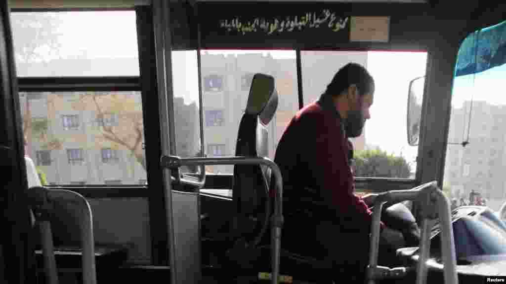 Bus driver Adel Abd El Fatah sits inside a damaged bus after a bomb blast near the Al-Azhar University campus in Cairo's Nasr City district, Dec. 26, 2013.