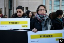 Human rights activists stage a protest demanding the release of Amnesty International's Taner Kilic, outside a court in Istanbul, Turkey, Jan. 31, 2018.