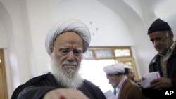 Một giáo sĩ iran bỏ phiếu tại một phòng phiếu ở thành phố Qom