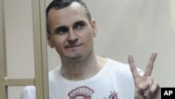 Ukrainian filmmaker Oleh Sentsov gestures as the verdict is delivered at his trial in Rostov-on-Don, Russia, Aug. 25, 2015.