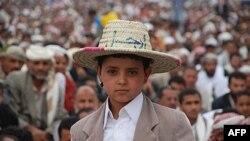 """Một bé trai đội chiếc nón với chữ Ả rập có nghĩa là """"hãy ra đi"""" trong một cuộc biểu tình chống chính phủ ở thủ đô Sana'a, Yemen"""