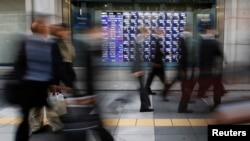 Passersby walk past stock quotation board outside brokerage, Tokyo, Dec. 4, 2013.