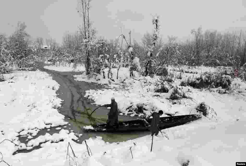 Warga Kashmir mencoba mendorong perahunya di perairan danau Anchar, setelah hujan salju melanda kota Srinagar, Kashmir-India.