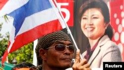 Người biểu tình chống chính phủ phất cờ quốc gia phía trước chân dung của Thủ tướng Thái Lan Yingluck Shinawatra bên ngoài văn phòng của Bộ Giao thông vận tải ở tỉnh Nonthaburi, ngoại ô Bangkok, ngày 29/1/2014.