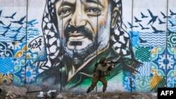 FILE - A member of the Israeli border guards looks through the scope of an assault rifle as he stands by a mural showing a graffiti image of late Palestinian leader Yasser Arafat, at the Qalandiya checkpoint near the West Bank city of Ramallah.