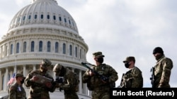 National Guard troops receive guns and ammunition outside the U.S. Capitol