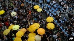 Người biểu tình cầm ô màu vàng để kỷ niệm một năm ngày xảy ra phong trào Chiếm Trung bên ngoài trụ sở của chính quyền Hong Kong hôm 28/9.