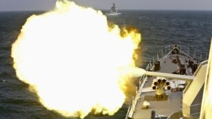 A Chinese navy vessel fires its cannon during the Joint Sea naval drill.