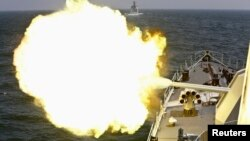 FILE - A Chinese navy vessel fires its cannon during joint exercises with the Russian navy in the East China Sea, May 24, 2014.