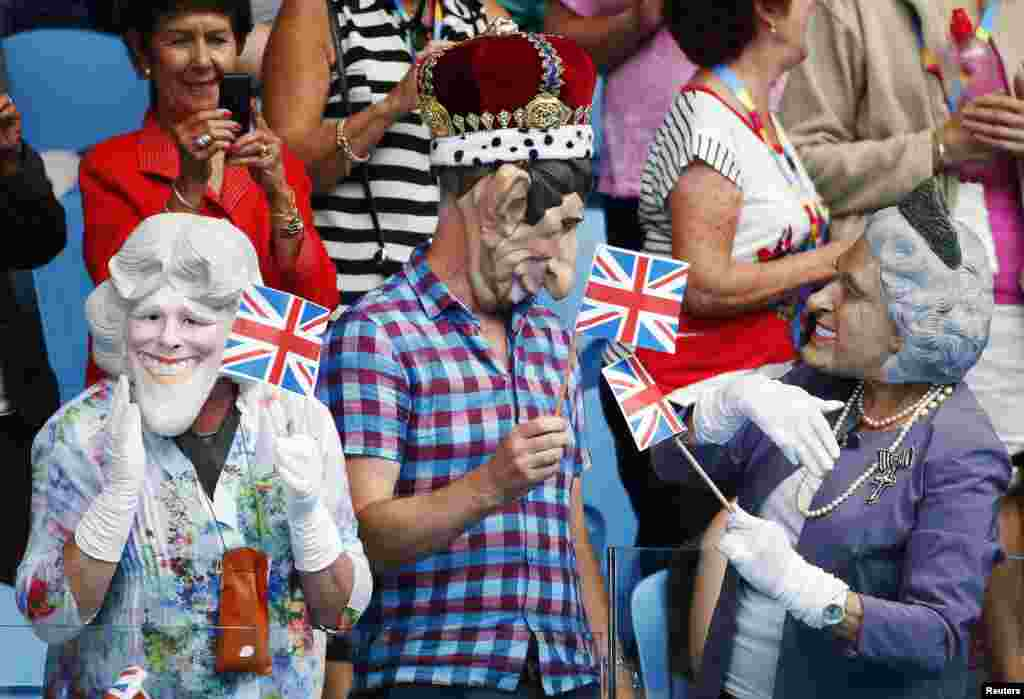 Spectators wearing masks depicting Britain's Royal family hold Union flags during the men's singles first round match between Andy Murray of Britain and Yuki Bhambri of India at the Australian Open 2015 tennis tournament in Melbourne.