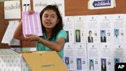 Wata jami'ar gudanar da zabe tana nuna katin zabe yayin kirga kuri'a a birnin Bangkok, Thailand.