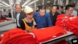 ນາຍົກລັດຖະມົນຕີຮຸນເຊນ (Hun Sen) (ກາງ) ກົ້ມເບິ່ງວຽກ ຂອງກໍາມະກອນຕັດຫຍິບ ໃນຂະນະທີ່ທ່ານໄປຢ້ຽມຢາມ ໂຮງງານຕັດຫຍິບແຫ່ງນຶ່ງ ຢູ່ນອກນະຄອນຫລວງພະນົມເປັນ ຂອງກໍາປູເຈຍໃນວັນທີ 30 ສິງຫາ, 2017.