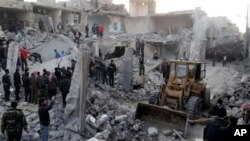 People gather around destroyed buildings after airstrikes hit areas in Aleppo, Syria, January 14, 2013.