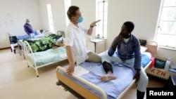 Un infirmier aide à traiter la tuberculose d'un patient à l'hôpital de Tugela en Afrique du sud, le 28 octobre 2008.