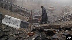 An elderly woman walks across a destroyed bridge toward the airport, the scene of heavy fighting in Donetsk, Ukraine, March 1, 2015.