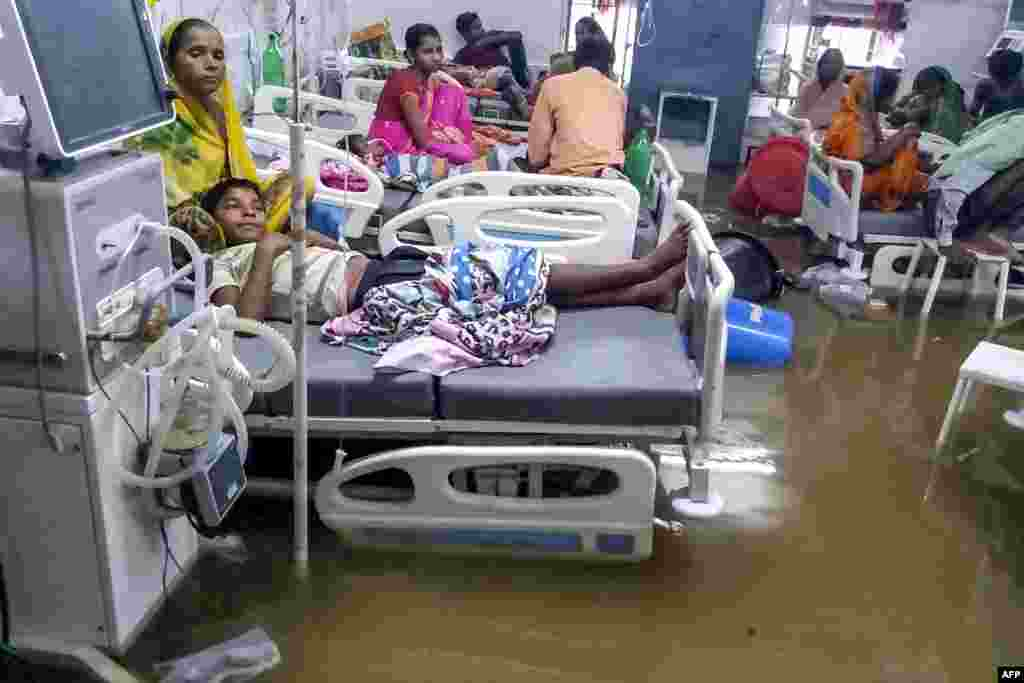Patients and their relatives rest in beds as they wade through floodwaters during heavy monsoon rain at waterlogged Nalanda Medical College and Hospital in Patna in the northeastern state of Bihar, India, Sept. 28, 2019.