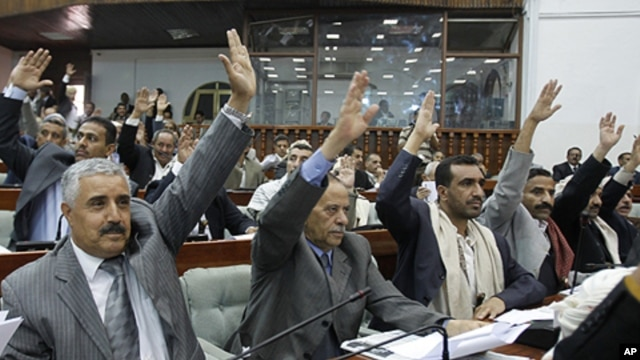 Members of Yemen's Parliament raise their hands to vote in favor of a law granting immunity to outgoing President Ali Abdullah Saleh over the killing of protesters, in Sana'a, January 21, 2012.