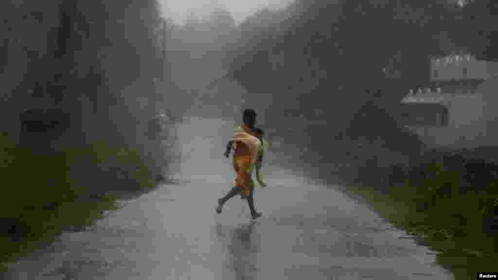 A girl runs for shelter in heavy rain brought by Cyclone Phailin in Ichapuram town in Srikakulam district in the southern Indian state of Andhra Pradesh.