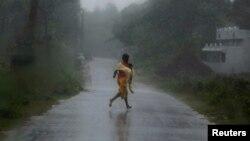 12일, 파일린으로 인한 폭우 속에 한 소녀가 긴급히 대피하고 있는 모습.