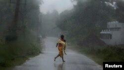 Une adolescente fuyant les pluies violentes du cyclone Phailin