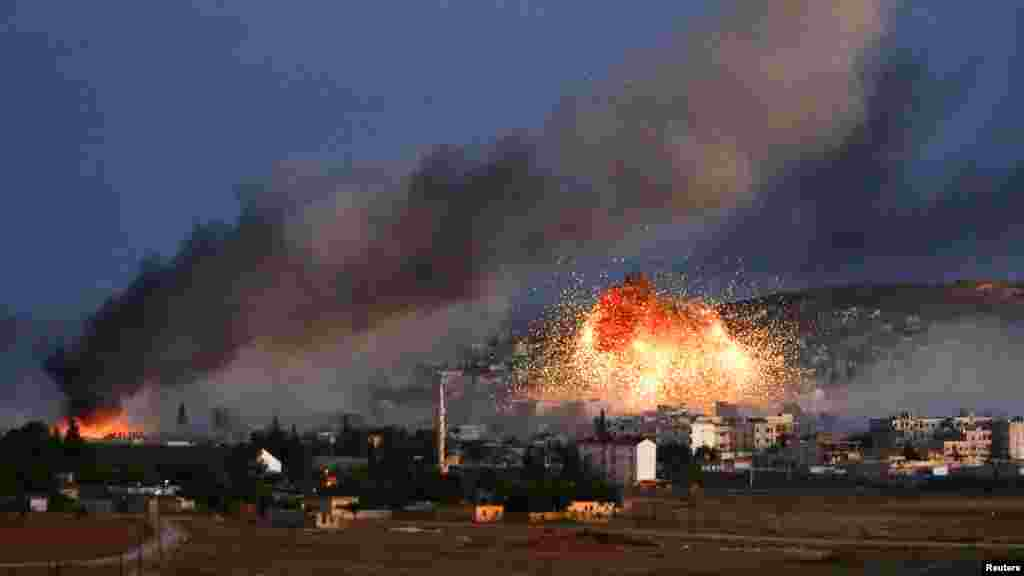 Smoke and flames rise over Syrian town of Kobani after an airstrike, as seen from the Mursitpinar crossing on the Turkish-Syrian border in the southeastern town of Suruc, Sanliurfa province, Oct. 20, 2014.