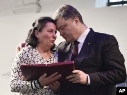 President Poroshenko presents a Hero of Ukraine award to a relative of an activist killed a year ago during mass protests, at the award ceremony in Kyiv, Feb. 20, 2015.