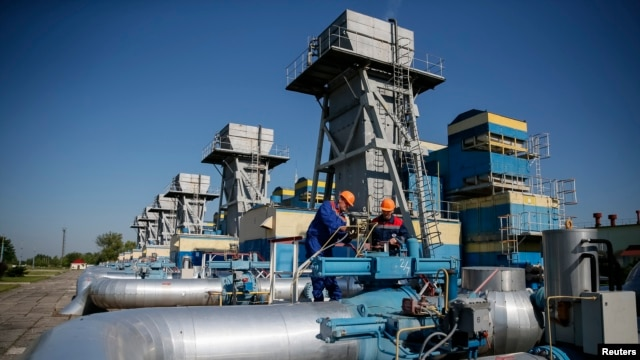 FILE - Workers stand near pipes at a gas compressor station near Uzhhorod May 21, 2014.