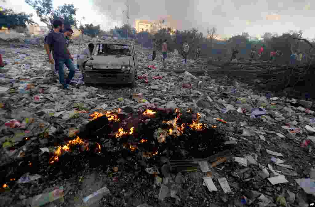 Palestinians look at a damaged vehicle amid debris in an area hit by an Israeli airstrike in Gaza City, July 24, 2014.